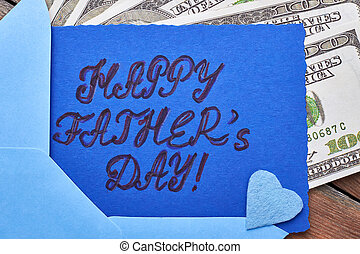 Dollars near Father's Day card. Blue fabric heart on card....