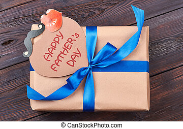 Card and gift for father. Present box on wooden backdrop....