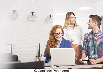 Co-worker using computer, man and woman discussing at work