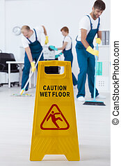 Wet floor sign and group of busy young cleaners working
