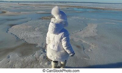 Girl child walks on the ice large lake. Girl is glad that the lake was frozen. The child can now slide on the ice. Sunny frosty winter day