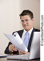 Close up of businessman with laptop working in boardroom