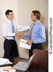 Two businessmen in office shaking hands - Two businessmen...