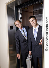 Businessmen in elevator looking out doorway