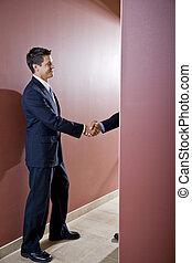 Businessmen shaking hands in office corridor