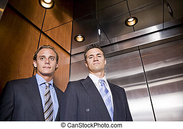 Businessmen riding in elevator, serious expression