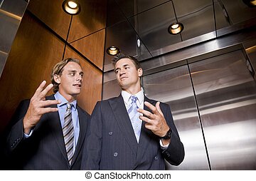 Businessmen riding in elevator conversing