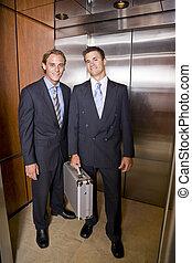 Businessmen standing in elevator