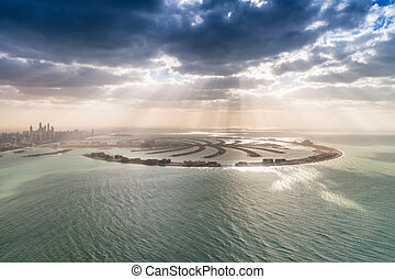 Stunning aerial view of Palm Jumeirah at sunset with sun rays on the ocean - Dubai
