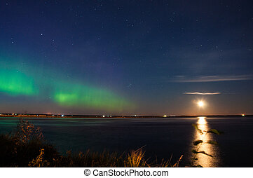 Intense Aurora borealis (northern lights) in moon lit night...
