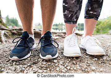 Legs of unrecognizable running couple in sports shoes