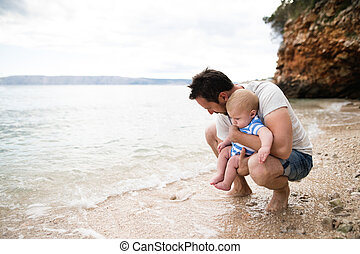 Man with his baby son at the beach having fun. - Handsome...
