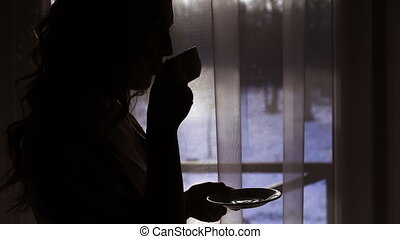 Night silhouette of woman drinking a cup of beverage near...