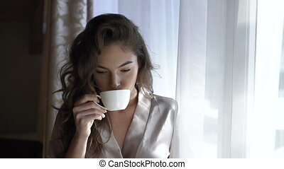 Pretty girl in nighty drinks a cup of coffee near the window