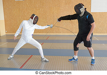 Two people in fencing competition