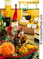 Santa Claus with pumpkins in a greengrocer