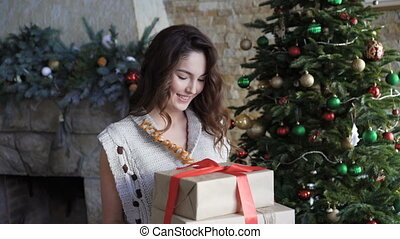 Happy girl holding christmas gifts and looking through...