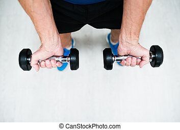 Hands of senior man in gym working out with weights