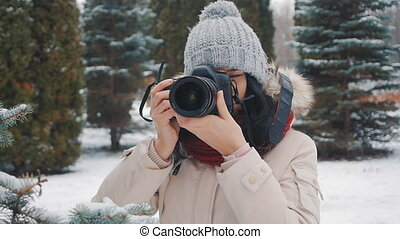 woman photographer takes shots in winter snow-covered park