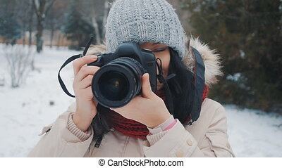 Beautiful young female photographer taking pictures at winter time in the park.