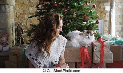 Pretty girl relaxing and playing with cat near christmas tree 4K