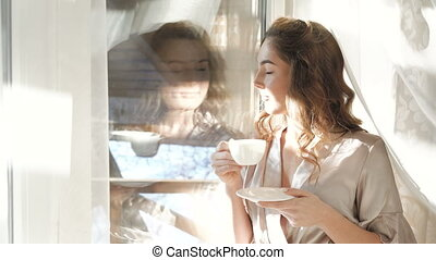 Reflection in the window of woman drinking a cup of beverage...