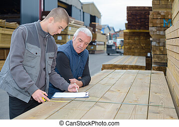 Men looking at clipboard and measuring wood