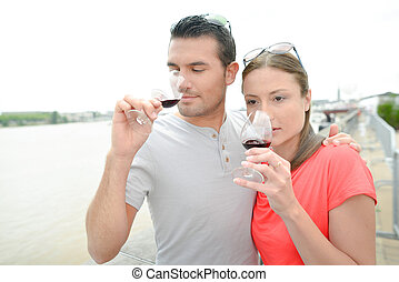 Couple drinking wine by the river