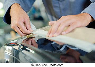 Applying masking tape to car bodywork