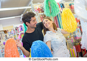 Couple playing with pompoms in a shop
