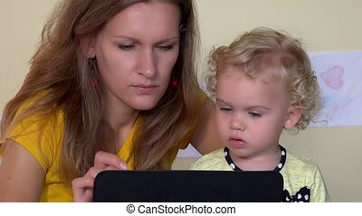 Serious face woman teaching baby girl using tablet computer. Closeup