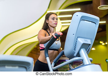 Fit woman doing cardio in an elliptical trainer in a gym. -...