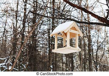 bird feeder on tree branch in forest in winter - wooden bird...