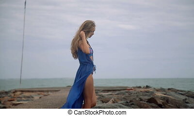 Gorgeous young girl with a beautiful figure posing and walks...