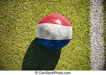 football ball with the national flag of netherlands lies on...