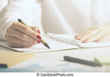 Woman writing in notepad - Woman writing in spiral notepad...