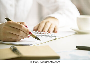 Female writing in notepad - Female writing in spiral notepad...