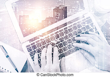 Male hands using laptop on city background. Double exposure....