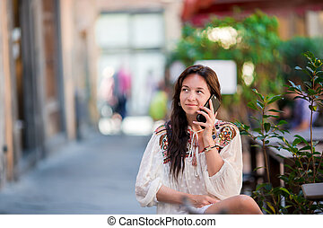 Portrait of beautiful woman sitting in outdoor cafe drinking...