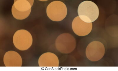 Hanging on the Christmas tree garlands sparkle brightly. Bokeh