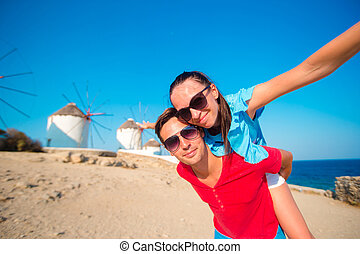 Young couple taking selfie with a stick in front of...