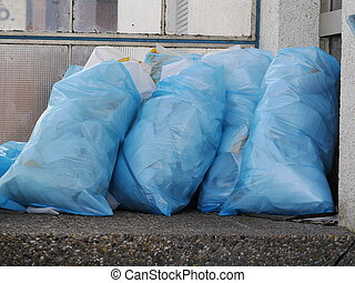 a pile of full garbage bags in a dump outdoors
