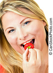 Young blond woman eating ripe strawberry - Portrait of young...