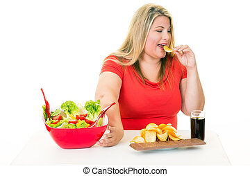 Woman pushing away salad and eating junk food - Overweight...