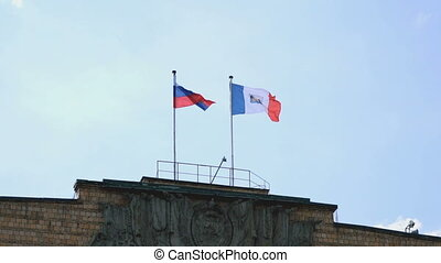 Waving flags of Russia and Velikiy Novgorod in sky -...