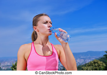 Portrait Of Young Woman Drinking Water After Jogging.