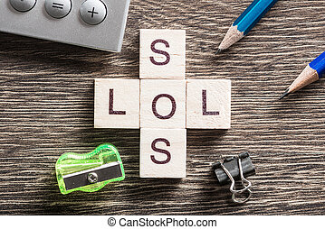 Words SOS and LOL on table made of wooden cubes elements -...