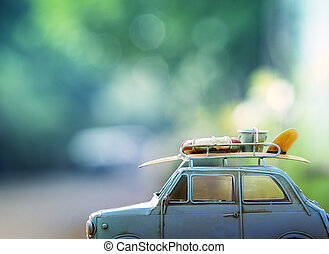old classic retro car with surf board and beach tool on roof...