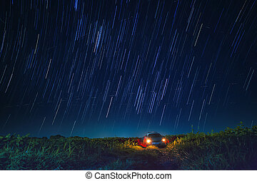 night scene of star tail and blue sky over car parking in...