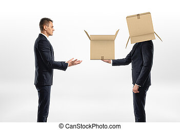 Businessman with cardboard box on his head passed another one to man
